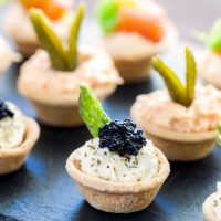 Multiple mini puff pastry tartlets with savory filling.